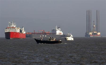 A small trawler passes in front of merchant vessels anchored outside the port of Mumbai, April 9, 2013. REUTERS/Vivek Prakash