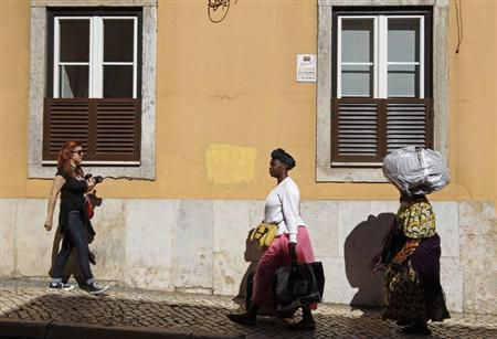 Women walk on a downtown street carrying their belongings in Lisbon April 17, 2013. REUTERS/Jose Manuel Ribeiro