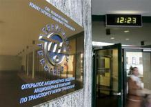 Женщина выходит из здания офиса компании Транснефть в Москве, 9 января 2007 года. Российская трубопроводная госмонополия Транснефть снизила чистую прибыль по МСФО без учета доли миноритариев до 180,5 миллиарда рублей в 2012 году со 188,1 миллиарда в 2011 году на фоне роста расходов и налогов. REUTERS/Anton Denisov