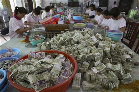 Employees count banknotes and coins received as tickets fee at a bus company in Haikou, Hainan province, April 17, 2013. REUTERS/Stringer