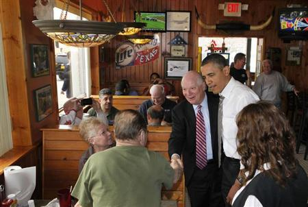 U.S. President Barack Obama stands next to U.S. Sen. Ben Cardin (D-Md) while greeting customers at the Texas Ribs & BBQ restaurant in Clinton, Maryland March 15, 2012. REUTERS/Larry Downing