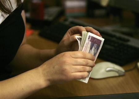 Latvia's Central Bank employee counts 10 lats (about 20 USD) banknotes in Riga June 5, 2009. REUTERS/Ints Kalnins