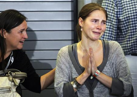 Amanda Knox (R) cries and gestures to friends while her mother Edda Mellas sits next to her during a news conference at Sea-Tac International Airport, Washington after Knox landed there on a flight from Italy, October 4, 2011. REUTERS/Anthony Bolante