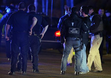 Law enforcement officers talk at the scene of a police manhunt in Watertown, Massachusetts April 19, 2013, following the shooting of a police officer at the Massachusetts Institute of Technology (MIT). REUTERS/Brian Snyder
