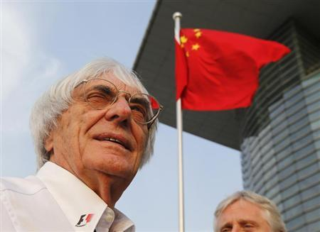 Formula One supremo Bernie Ecclestone is seen in front of Chinese national flag at a paddock after the qualifying session for the Chinese F1 Grand Prix at the Shanghai International Circuit, April 13, 2013. REUTERS/Kim Kyung-Hoon