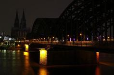 The UNESCO World Heritage Cologne Cathedral and the Hohenzollern railway bridge along the river Rhine are seen during Earth Hour March 23, 2013. REUTERS/Wolfgang Rattay