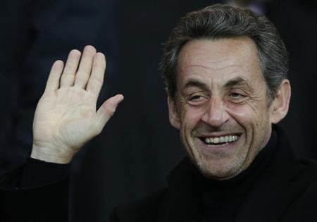 Former French President Nicolas Sarkozy waves as he attends the Champions League quarter-final first leg soccer match where Paris St Germain faces Barcelona at the Parc des Princes Stadium in Paris, April 2, 2013. REUTERS/Christian Hartmann