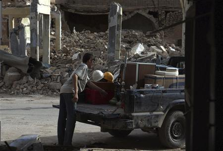 A boy loads a truck with the remains from his shop after it was damaged by what activist say was shelling by forces loyal to Syria's President Bashar Al-Assad Deir al-Zor April 17, 2013. REUTERS/ Khalil Ashawi