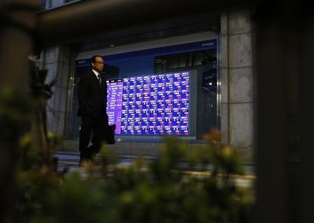 A man walking past an electronic board showing stock prices outside a brokerage, is pictured through a bamboo fence at a bush in Tokyo April 4, 2013. REUTERS/Yuya Shino