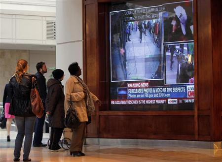 People stop to watch a breaking news report showing images of the two suspects in the Boston Marathon bombing, inside the Prudential Center in Boston, Massachusetts, April 18, 2013. REUTERS/Jessica Rinaldi