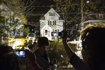 Neighbors use cameras to record images of the boat at 67 Franklin St. where Dzhokhar Tsarnaev, the surviving suspect in the Boston Marathon bombings, was hiding inside in Watertown, Massachusetts, April 19, 2013. REUTERS/Lucas Jackson