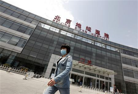 A woman wearing a mask walks outside the Ditan Hospital, where a child with a new strain of bird flu is undergoing treatment, in Beijing April 13, 2013. REUTERS/Jason Lee