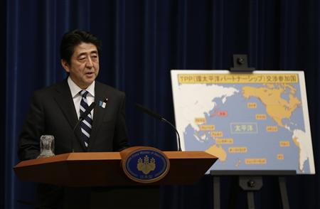 Japan's Prime Minister Shinzo Abe speaks next to a map showing participating countries in rule-making negotiations for the Trans-Pacific Partnership (TPP) during a news conference at his official residence in Tokyo March 15, 2013. REUTERS/Toru Hanai