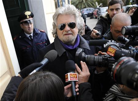 Five Star Movement leader and comedian Beppe Grillo speaks with media after casting his vote at the polling station in Genoa February 25, 2013. REUTERS/Giorgio Perottino