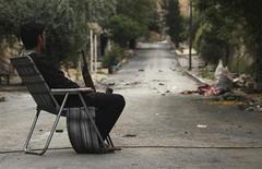 مقاتل من الجيش السوري الحر يحمل سلاحه في وسط احد الشوارع بمدينة حلب يوم الجمعة. تصوير. مالك الشمالي - رويترز