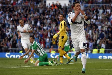 Real Madrid's Mesut Ozil (R) celebrates his goal during their Spanish First Division soccer match against Real Betis at Santiago Bernabeu stadium in Madrid April 20, 2013. REUTERS/Juan Medina