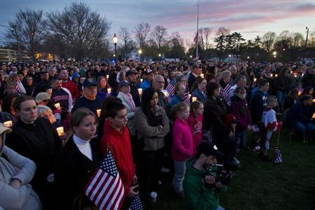 People hold candles during a vigil for slain MIT police officer Sean Collier at the Town Common in Wilmington, Massachusetts, April 20, 2013. REUTERS/Dominick Reuter
