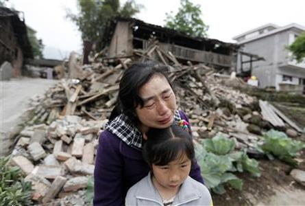 Song Zhengqiong, holding her daughter, cries in front of her damaged house after a strong 6.6 magnitude earthquake at Longmen village, Lushan county in Ya'an, Sichuan province April 21, 2013. REUTERS-Jason Lee (CHINA - Tags: DISASTER ENVIRONMENT TPX IMAGES OF THE DAY)