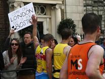 Espectadores seguram cartaz em homenagem às vítimas das explosões na Maratona de Boston durate a Maratona de Londres. Atletas na Maratona de Londres no domingo usaram fitas pretas e observaram 30 segundos de silêncio para homenagear as vítimas do atentado da Maratona de Boston, sob o olhar atento de um maior número de policiais destacados para tranquilizar o público. 21/04/2013 REUTERS/Eddie Keogh