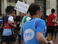 Spectators hold a placard in support of Boston as runners pass during the London Marathon in central London April 21, 2013. REUTERS/Eddie Keogh