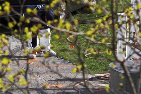 A member of the FBI Evidence Recovery Team spray paints around spent shotgun shells in the yard where Boston Marathon bombing suspect Dzhokhar Tsarnaev was hiding at 67 Franklin St. in Watertown, Massachusetts, April 20, 2013. REUTERS/Lucas Jackson