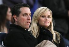 Actress Reese Witherspoon (R) and her husband Jim Toth watch the Toronto Raptors play the Los Angeles Lakers in their NBA basketball game in Los Angeles, March 8, 2013. REUTERS/Lucy Nicholson