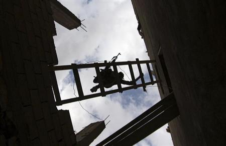 A Free Syrian Army fighter carries his weapon as he uses a ladder to climb into a building in Deir al-Zor April 20, 2013. REUTERS/Khalil Ashawi