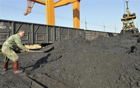A worker uses a shovel to pile up iron ore next to a freight train at a railway station in Yingtan, Jiangxi province December 17, 2010. REUTERS/Stringer