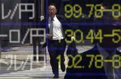 """Бегущий мужчина отражается в информационном табло с курсами валют в Токио, 22 апреля 2013 года. Курс иены вновь близок к 100 за доллар, так как """"Большая двадцатка"""" не стала критиковать Японию за денежно-кредитную политику, вызвавшую значительное ослабление иены. REUTERS/Toru Hanai"""