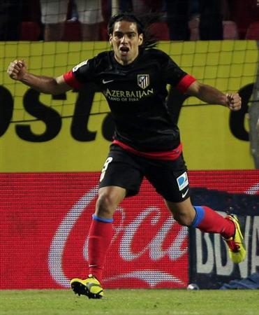 Atletico Madrid's Radamel Falcao celebrates after scoring against Sevilla during their Spanish First Division soccer match at Ramon Sanchez Pizjuan stadium in Seville April 21, 2013. REUTERS/Marcelo del Pozo
