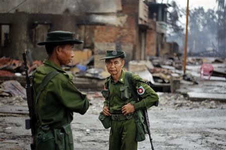 Soldiers patrol through a neighbourhood that was burnt during recent violence in Sittwe June 14, 2012. REUTERS/Soe Zeya Tun