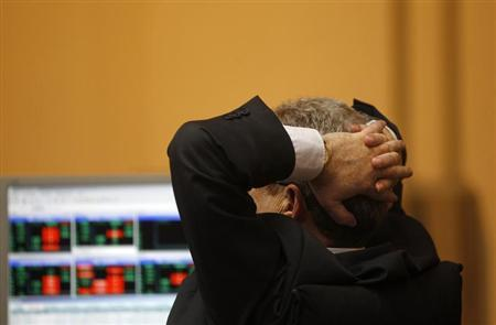 A trader reacts as he looks at screens during trading at the Madrid bourse April 19, 2012. REUTERS/Susana Vera