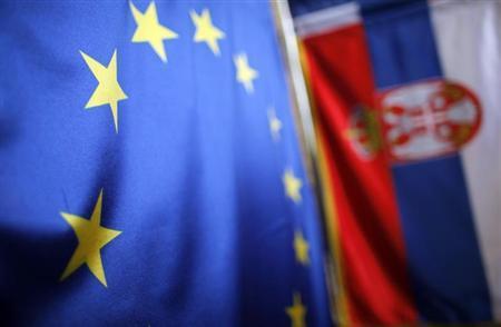 Serbian (R) and EU flags are seen inside a shop in Belgrade December 8, 2011. REUTERS/Marko Djurica