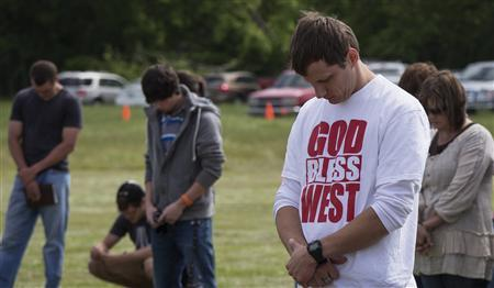 Town residents bow their heads in prayer during an open air Sunday church service four days after a deadly fertilizer plant explosion in the town of West, near Waco, Texas April 21, 2013. REUTERS/Adrees Latif