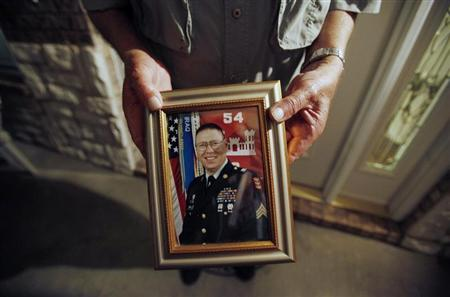 Wilburn Russell, 73, displays a portrait of his son, Sergeant John M. Russell, the Army sergeant who is accused of killing five fellow soldiers in Iraq, outside of his son's home in Sherman, Texas May 12, 2009. REUTERS/Jessica Rinaldi
