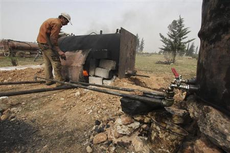 A man works at a makeshift oil refinery site in Aleppo's countryside April 2, 2013. REUTERS/Giath Taha
