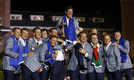 Team Europe captain Jose Maria Olazabal (C) of Spain is lifted up as he poses with golfers (L-R), Sergio Garcia, Paul Lawrie, Ian Poulter, Rory McIlroy, Nicolas Colsaerts, Lee Westwood, Justin Rose, Graeme McDowell, Francesco Molinari, Peter Hanson, Luke Donald and Martin Kaymer while holding the Ryder Cup after the closing ceremony of the 39th Ryder Cup at the Medinah Country Club in Medinah, Illinois, September 30, 2012. REUTERS/Mike Blake