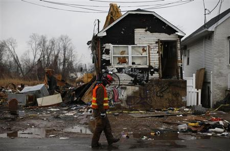 A worker walks past as a house damaged beyond repair by Hurricane Sandy is demolished by heavy machinery in the Ocean Breeze neighborhood of Staten Island in New York City, January 16, 2013. REUTERS/Mike Segar