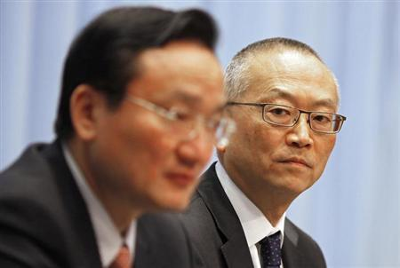 Keiji Fukuda (R), assistant director-general for Health Security and Environment of World Health Organization (WHO), looks at a Chinese health official during a news conference in Shanghai April 22, 2013. REUTERS/Carlos Barria