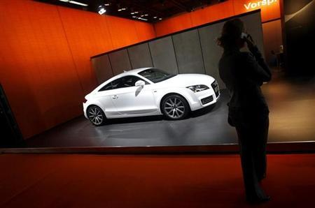 A woman talks on her mobile phone as she stands next to Audi's ''TT Coupe 3.2 Quattro'' car at the Auto Expo in New Delhi January 9, 2008. REUTERS/Adnan Abidi/Files