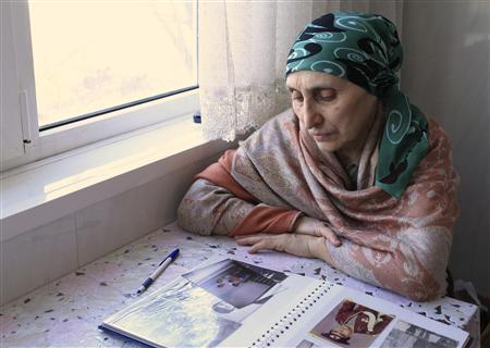 Patimat Suleimanova, aunt of Boston bombing suspects Dzhokhar and Tamerlan Tsarnaev, looks at photos from a family album at her house in Makhachkala, April 22, 2013. REUTERS/Stringer