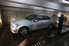 A worker washes a Mercedes-Benz car at its garage in Mumbai April 19, 2013. Luxury carmakers in India are moving downmarket and shifting production of smaller and cheaper cars to local plants to cut costs, broadening their target market to include India's young, female and middle-class drivers to boost lacklustre performance. Mercedes, which has built cars in India since 1995, is doubling assembly capacity at its plant in Pune in western India to 20,000 cars annually this year, and will bring its A-Class small cars to the country in the next three months. It is also introducing guaranteed resale prices across its range, and adding cars like its GL-Class to its local plant this year. REUTERS/Vivek Prakash