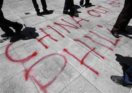 Graffiti done by activists is seen in front of the Chinese consulate demanding the withdrawal of Chinese ships from the disputed Scarborough Shoal in the South China Sea during a protest in Manila's Makati financial district in this April 19, 2012 file photo. REUTERS/Cheryl Ravelo/Files