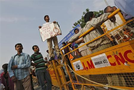 A protester holds a placard as he stands on top of a police barricade during a protest outside the hospital where a five-year-old girl who was raped and tortured is admitted in New Delhi April 22, 2013. REUTERS/Adnan Abidi