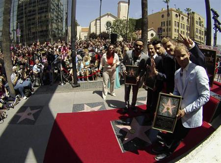 Backstreet Boys (from L-R) A. J. McLean, Howie Dorough, Kevin Richardson, Nick Carter and Brian Littrell pose by their star after it was unveiled on the Walk of Fame in Los Angeles, California April 22, 2013. REUTERS/Mario Anzuoni