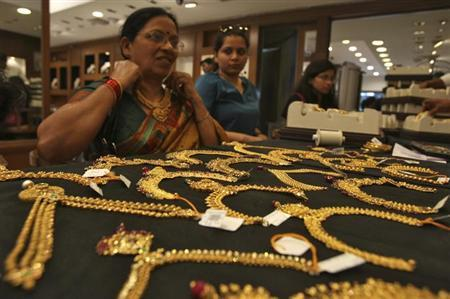 A customer tries on a gold necklace inside a jewellery showroom in Hyderabad April 11, 2012. REUTERS/Krishnendu Halder/Files