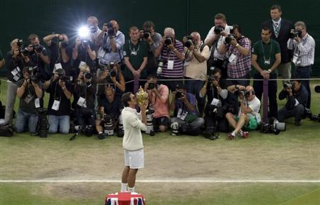 Roger Federer of Switzerland kisses the winners trophy after defeating Andy Murray of Britain in their men's singles final tennis match at the Wimbledon Tennis Championships in London July 8, 2012. REUTERS/Clive Rose/Pool/Files