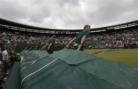 The covers are pulled over number one court as rain stops play in the match between Fernando Verdasco of Spain and Ivo Karlovic of Croatia at the Wimbledon tennis championships in London, June 29, 2009. REUTERS/Eddie Keogh