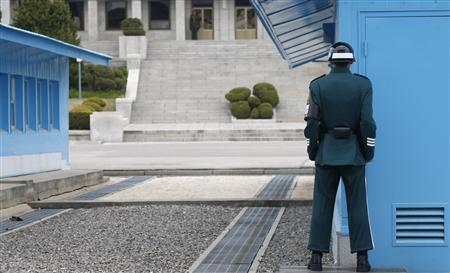 A North Korean soldier (top L) keeps watch as a South Korean soldier watches north at the truce village of Panmunjom in the demilitarized zone dividing the two Koreas, in Paju, about 55 km (34 miles) north of Seoul April 23, 2013. REUTERS-Lee Jae-Won