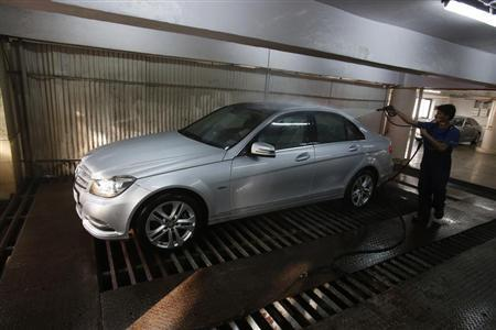 A worker washes a Mercedes-Benz car at its garage in Mumbai April 19, 2013. REUTERS/Vivek Prakash